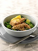Sliced chicken breasts coated in sesame seeds with broccolis and lemon