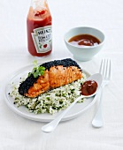 Piece of salmon coated with black sesame seeds,rice with herbs