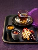 Verschiedene Waffeln mit zweierlei Fruchtsaucen und einer Tasse Tee
