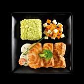 Gebratener Lachs mit Gemüse und grünem Püree auf einem schwarzen Teller