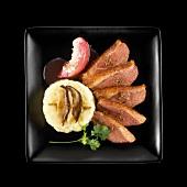Entenbrust mit weisser Pfirsichsauce, Kartoffelpüree und Pilzen auf schwarzem Teller