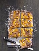 Süsse Pizza mit Pfirsichen, Mandeln und Puderzucker in Stücke geschnitten