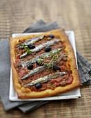 Pizza mit Gemüse, Sardinen, schwarzen Oliven und Thymian