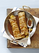 Rolled crepes garnished with apples and salted butter toffee sauce
