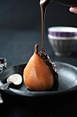 Pouring melted chocolate over a poached pear