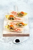 Chicory boats garnished with marinated salmon, pickles and carrots