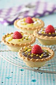 White and dark chocolate,crushed pistachio and raspberry tartlets