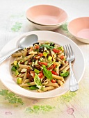 Pasta salad with fresh and dried tomatoes, avocado and basil