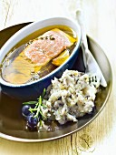 Piece of salmon marinating in olive oil, mashed potatoes with black olives