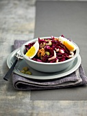 Red cabbage, celery stalk, hard-boiled egg and walnut salad