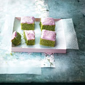 Cubes of geen tea cake with pink frosting