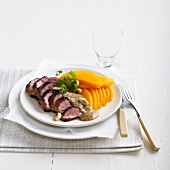 Duck fillets with almond sauce and thinly sliced mango