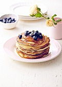 Stack of pancakes with blueberries and honey