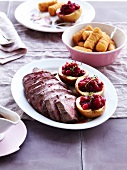 Roast boar with gravy, apples stuffed with cranberry jam, potato croquettes