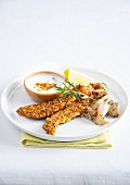 Fingers of whiting coated in curry, sesame seeds and rosemary, herby white sauce