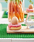 Donut topped with an egg,figurine name-tag,bunch of carrots in a jar of water