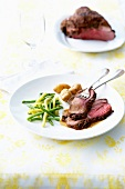 Roasted leg of lamb in pepper crust with green and yellow beans and potatoes