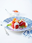 Cold tomatoes stuffed with diced yellow and red peppers and feta cream