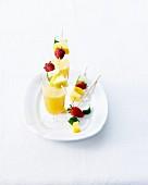 Alkoholfreier Cocktail mit Mango und Ananas, Spiesse mit frischen Früchten