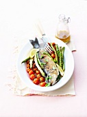 Grilled sea bass with basil, cherry tomatoes and raw grilled green asparagus