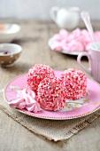 Drei pinke Merveilleux (französische Meringuetörtchen) mit rosa Zuckerdekor
