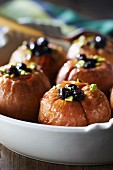 Baked apples garnished with crushed pistachios and macerated blackcurrants