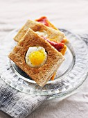 Ham and cheese toasted sandwich topped with a fried quail's egg