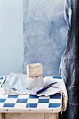 Weichkäse mit Käsemesser und Papier auf weiss-blau karierter Tischplatte