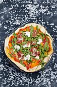 Pizza with cured ham, mozzarella di bufala and rocket salad