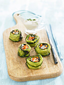 Cucumber sushi with guacamole and vegetables, yogurt sauce