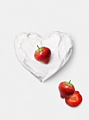 Whipped cream heart topped with a strawberry