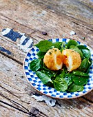 Breaded soft-boiled egg with raw baby spinach