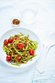 Spinach tagliatelle with tomatoes and pine nuts