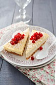 Two pieces of cheesecake with coconut and red currants