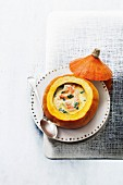 Cream of pumpkin soup with shrimps served in a pumpkin shell