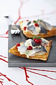 Toasted polar bread toped with rollmops and sweet and sour cream