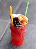 Glass of watermelon-strawberry granita topped with fresh fruit