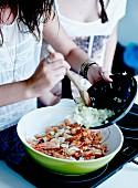 Frau bereitet Fischsud mit Zwiebeln, Köpfen und Schalen von Garnelen zu