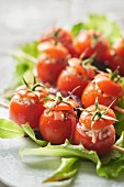Small tomatoes stuffed with raw ham and button mushrooms on skewers