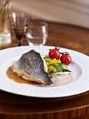 Sea bream with cherry tomatoes and yellow and green courgettes