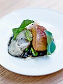 Sea-land dish,crisp greens on a bed of squid ink