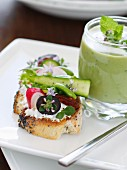 Cold minty cream of pea soup ,goat's cheese and vegetables on sliced bread