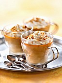 Coffee cream dessert topped with whipped cream and sprinkled with speculos ginger biscuit crumbs