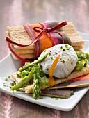Knuspriges Gebäck mit grünem Spargel, pochiertem Ei, Schnittlauch und rosa Pfeffer