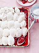 Vanilla-flavored stewed strawberries topped with meringue and sprinkled with icing sugar