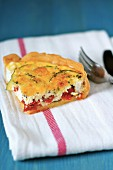 Slice of feta,tomato and zucchini quiche