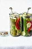 Eingemachte Gurken mit Chili und Gewürzen in Einweckgläsern