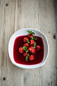 Strawberry soup with hibiscus flower syrup and mint