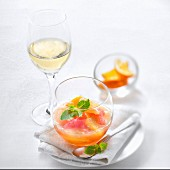 Citrus fruit mishmash with mint, glass of fruity white wine