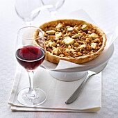 Tart with onion confit, pine nuts and goat cheese, served with a glass of red wine